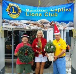 Lions Cliff, Debbie and Joe Displaying our Wreaths , and Small tree assortment. Purchase Your Christmas Tree From the Sanibel-Captiva Lions Club Stand on Periwinkle in the Baileys Shopping Center